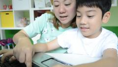 Stock Video Footage of Happy Asian Mom is teaching her son Using Laptop