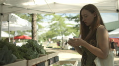 Woman shops with smart phone at farmers' market HD Stock Footage