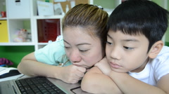 Stock Video Footage of lazy Asian Mom is teaching her son Using Laptop