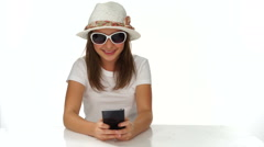 Trendy young teenager smiling as she reads an sms Stock Footage