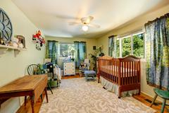 Nursery room with crib and old bed Stock Photos