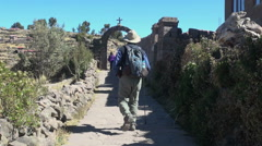 Peru Taquile man walks path toward stone arch 12 Stock Footage