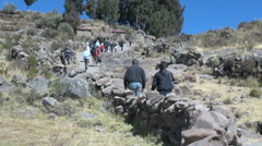 Peru Taquile climbing hill toward arch and trees 26 Stock Footage