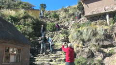 Peru Taquile tourists on steep steps on hillside 23 Stock Footage