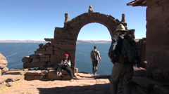 Peru Taquile people walk and take photos near stone arch 17 Stock Footage