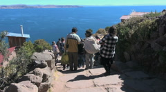 Peru Taquile tourists descend steps toward lake 24 Stock Footage