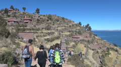 Peru Taquile hillside tourists walk through arch side view 27 Stock Footage