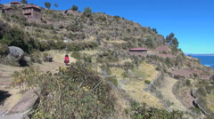 Peru Taquile hillside woman approaches with heavy load  Stock Footage