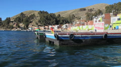 Peru Lake Titicaca flags and dock recede as boat leaves  Stock Footage