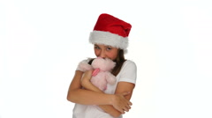 Young girl in a Santa Hat kissing a teddy bear Stock Footage