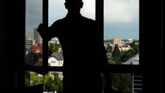 Man close the window - silhouette - city (buildings with nature in background) Stock Footage