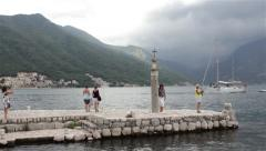 Tourists visit old sea town and monument statue in the port. Sailboat passing. Stock Footage