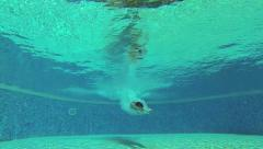 Man jumping into the swimming pool, steadycam shot, slow motion shot at 120fps Stock Footage