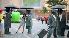 """People toting umbrellas"" sculpture Stock Footage"