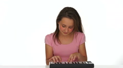 Young girl playing music on a small keyboard Stock Footage