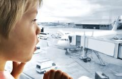 Cute boy looking at planes in the airport with great interest Stock Photos