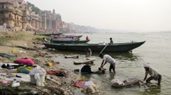 People wash clothes in Ganga river. Stock Footage
