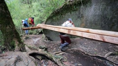 Porters carry heavy wooden beams Stock Footage