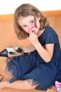 Little cute girl posing while panting her face - stock photo