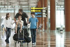 Family pushing luggage cart in airport Stock Photos