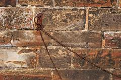 Old Stonewall Background Rusted Iron Ring and Chain - stock photo
