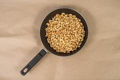 roasted cashews in frying pan on paper - stock photo