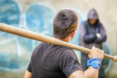 Aggressive teenager with a baseball bat against man at outdoor Stock Photos