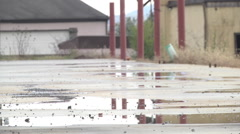 Urban decay industrial landscape potholes rainwater and structures Stock Footage