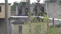 Urban decay industrial landscape telephoto abandoned and overgrown Stock Footage