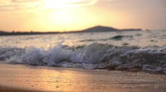 Closeup of Sea Waves on Sandy Beach at Sunset. Slow Motion. Stock Footage