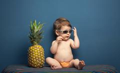 Happy baby girl playing with a pineapple - stock photo