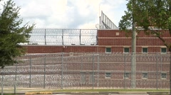 Prison, Federal, three tiers razor wire & building - stock footage