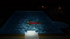 Young Girl Swims in the Pool at Night. Slow Motion. Stock Footage