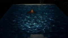Woman Swims in the Swimming Pool at Night. Slow Motion. Stock Footage