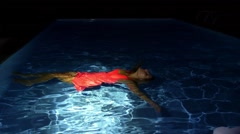 Young Woman in Bright Dress Lying on the Pool Water at Night. Stock Footage