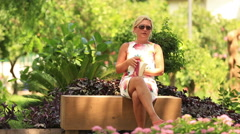 blonde women reading book in the park with back pain - stock footage