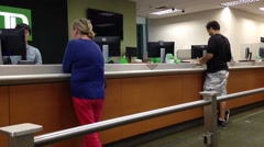 People at a service counter talking to the teller Stock Footage