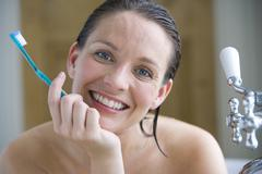 Young woman with toothbrush in bath, chin in hand, smiling, portrait, close-u Stock Photos