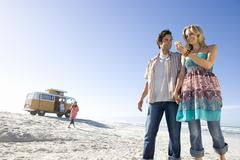 Stock Photo of young couple holding hands on beach, woman looking at shell, low angle view