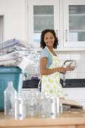 young woman washing glass jar and can for recycling, smiling (differential fo - stock photo