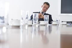 Businessman at conference table looking at watch, low angle view Kuvituskuvat