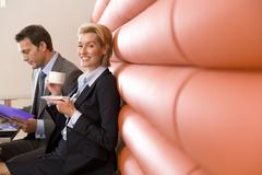 Businessman and woman having meeting in booth in cafe, woman with coffee cup, Kuvituskuvat