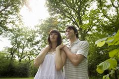 Young couple outdoors, man with hands on woman's shoulders, low angle view (l Stock Photos