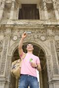 Man taking photograph of himself by archway, smiling, low angle view Stock Photos