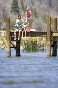 Family of four fishing from jetty, low angle view Stock Photos
