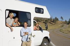 Family of four with motor home, man with map by son and daughter (8-12), moth Stock Photos