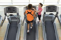 Fitness instructor training man on treadmill in gym, elevated view Stock Photos