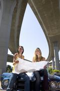 Two young women on bonnet of car looking at road map beneath overpass, smilin Stock Photos