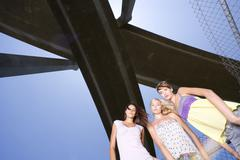 small group of friends beneath overpass, portrait, low angle view - stock photo