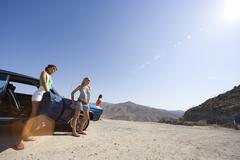 Small group of friends by car in desert, looking at view, low angle view (len Stock Photos